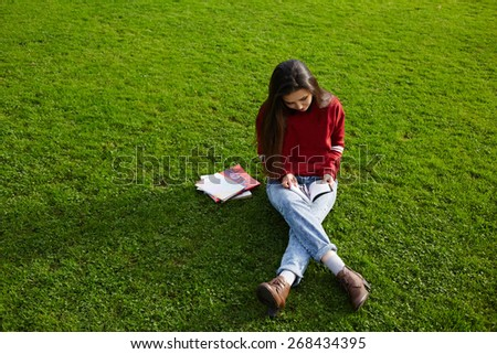 Pretty student girl sitting on the grass reading a book outdoors, young attractive girl with brunette long hair seating on the copy space grass background holding some book in the hands - stock photo