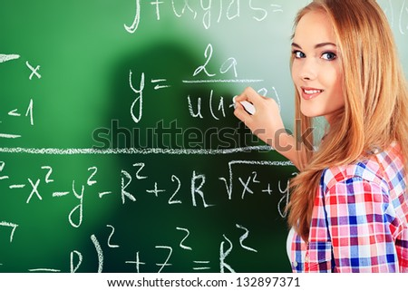 Pretty student girl standing at the blackboard in the classroom. - stock photo