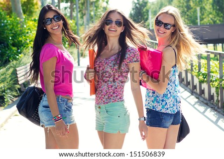Pretty student girls having fun at the park after school - stock photo