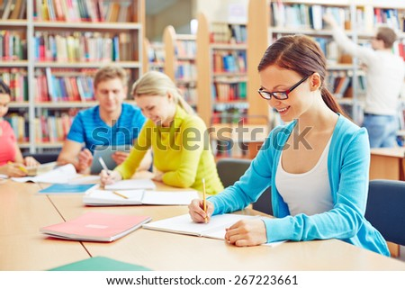 Pretty student making notes in college library - stock photo