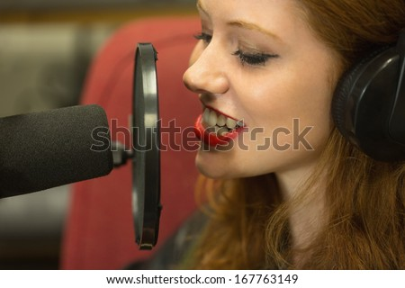 Pretty student presenting a radio show in college - stock photo