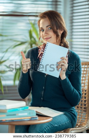 Pretty student showing thumb up and a blank notebook - stock photo