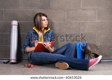 Pretty student sitting near the wall and writing at notebook - stock photo