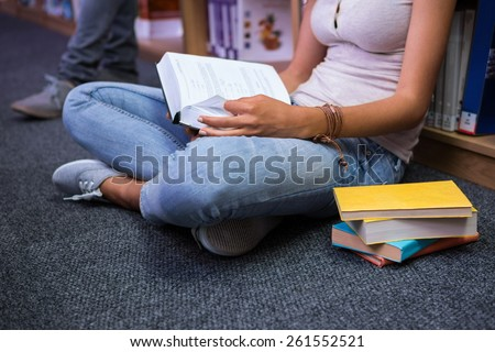 Pretty student sitting on floor reading book in library at the university - stock photo