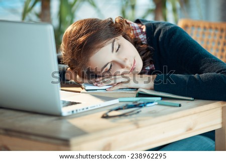 Pretty student sleeps instead of learning - stock photo