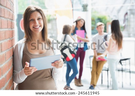 Pretty student smiling and holding tablet at the university - stock photo