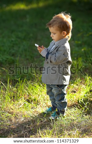 Pretty stylish baby boy standing in the park and writing sms on his mobile (cell) phone . Outdoor shot. - stock photo