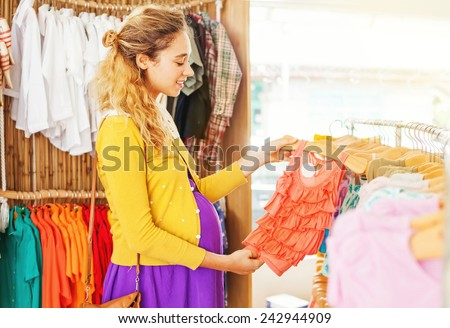 Pretty stylish pregnant woman choosing clothes in the shop for her future newborn daughter - stock photo