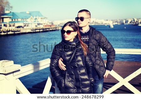 Pretty stylish young couple. Couple of young people in fashion clothes posing outdoors.  - stock photo