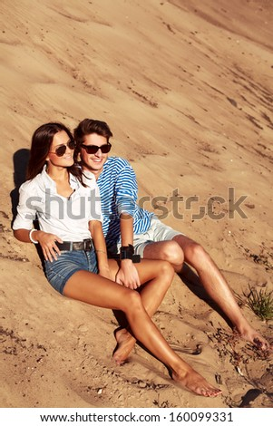 Pretty stylish young couple having fun in summer on the beach - stock photo
