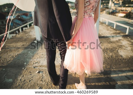 Pretty sunny outdoor portrait of young stylish couple while kissing on the roof with city view