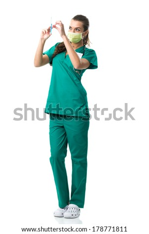 Pretty surgeon in green mouth mask,holding the  injection - stock photo
