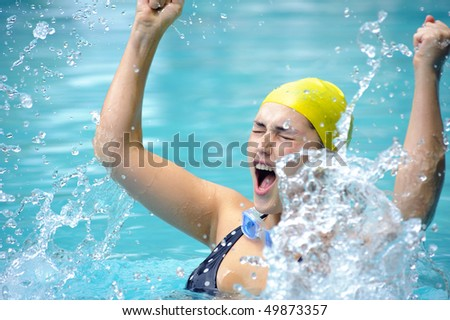 Pretty swimmer is happy and splashes in the water - stock photo