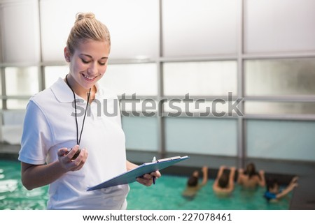 Pretty swimming coach standing poolside at the leisure center - stock photo