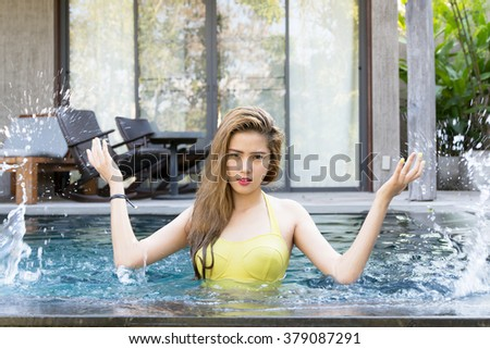 Pretty swimsuit fashion young sexy asian woman posing in pool - stock photo