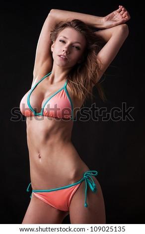 Pretty tanned woman in bikini on black background. - stock photo