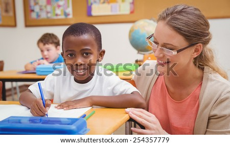 Pretty teacher helping pupil in classroom at the elementary school - stock photo