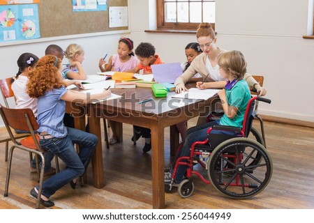 Pretty teacher helping pupils in classroom at the elementary school - stock photo