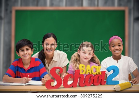 Pretty teacher helping pupils in library against blackboard with copy space on wooden board - stock photo