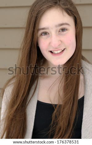 Pretty teen-aged girl with long brown windblown hair smiling in beige and black with beige background