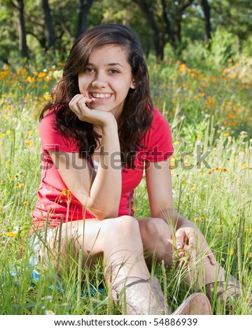 Pretty teen girl in a field of wildflowers