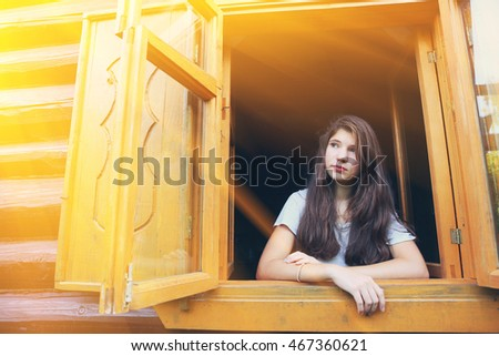 pretty teen girl in country wooden window with shades and log house wall