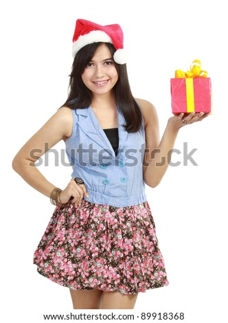 Pretty teen girl in Santa hat presenting gift isolated on white - stock photo