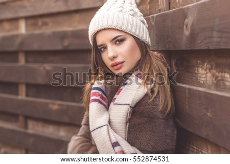Pretty teen girl is wearing warm hat and scarf