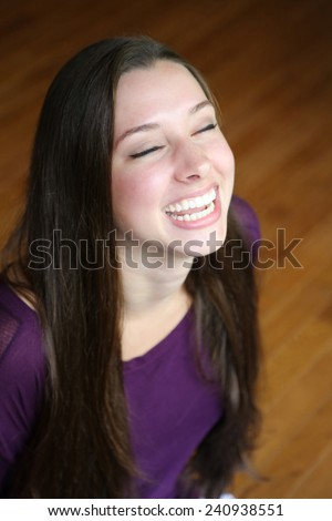 pretty teen girl laughing with eyes closed - stock photo