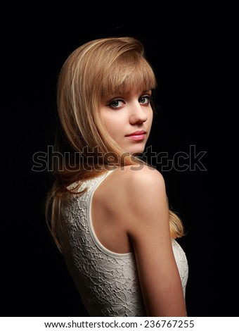 Pretty teen girl posing with blond long hair style and pink lipstick on black background - stock photo
