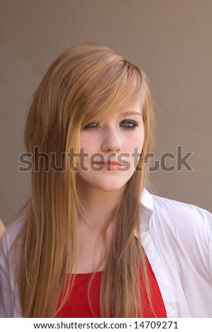 Pretty teen girl smiling (sorta) shot against dark background