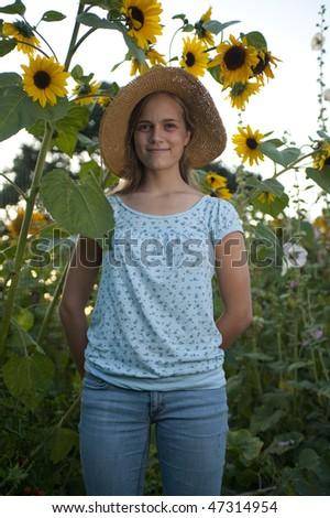Pretty teen girl standing beside tall sunflowers - stock photo
