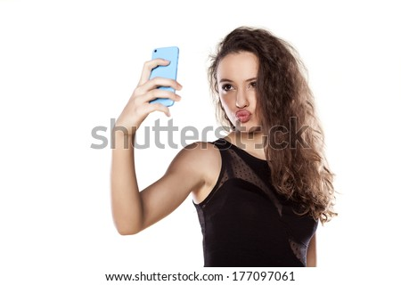 pretty teen girl taking selfies with her smart phone - stock photo