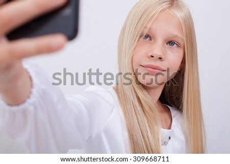 pretty teen girl taking selfies with her smart phone on white background - stock photo