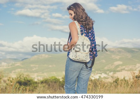 Pretty teen girl with bag over nature background