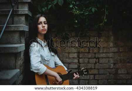 Pretty Teen Girl with Guitar Posing in the Patio. Beautiful Art Background - stock photo