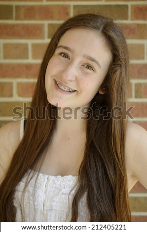 Pretty teen girl with long brown hair and braces smiling with brick background - stock photo