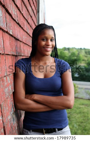 pretty teen standing against red weathered shingles
