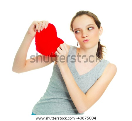 pretty teenage angry girl tearing a heart-shaped pillow into pieces - stock photo