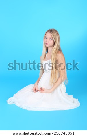 pretty teenage blond girl in the white dress over the blue background - stock photo