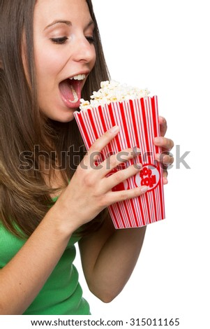 Pretty teenage girl eating popcorn - stock photo