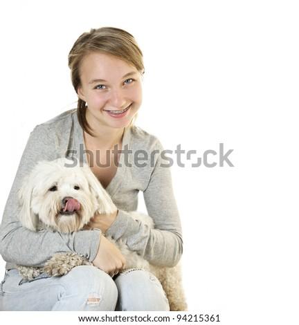 Pretty teenage girl holding adorable coton de tulear dog - stock photo