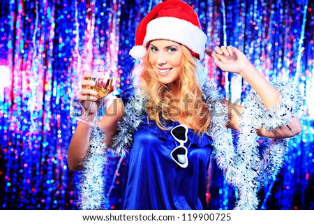 Pretty teenage girl in Christmas clothes on a party. Disco lights in the background.