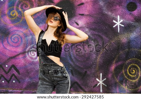 pretty teenage girl posing outdoors dressed casual on colorful graffiti wall - stock photo
