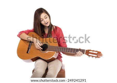 Pretty teenage girl singing a song while playing an acoustic guitar isolated over white background - stock photo