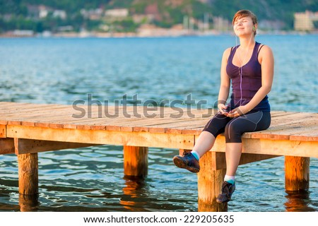 Pretty teenage girl sitting on a wooden pier and listening to music - stock photo