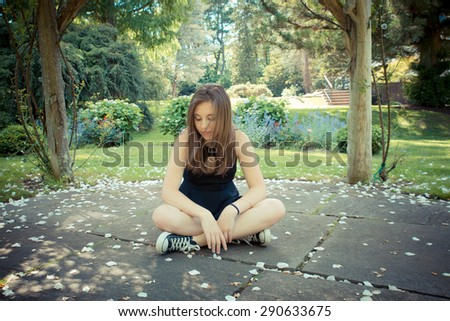 Pretty teenage girl sitting on ground in garden with soft filter effect - stock photo