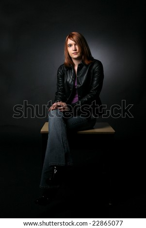pretty teenage girl sitting on student desk