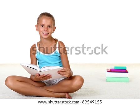 Pretty teenage girl sitting on th efloor with study books - stock photo