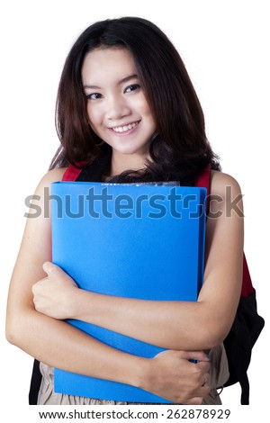 Pretty teenage girl smiling at the camera while carrying a backpack and a folder, isolated over white - stock photo